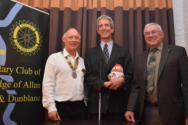Ken Reid (centre) holding Haggeye (his mascot on the journey) with president Nick Rawlings (left) and speaker's host Glen Montgomery
