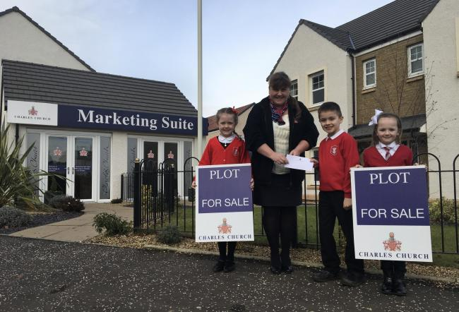 Persimmon Homes East Scotland sales executive Sharon Thomson hands a donation over to pupils from East Plean Primary School and Nursery