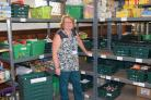 Adrienne Hilton, foodbank coordinator, next to the shelves which would normally be full